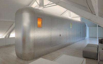 Airstream-inspired pod hides bathrooms, entertainment center.