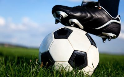 Player balances cleated foot on a soccer ball.