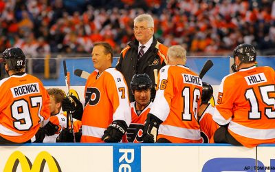 Members of the Philadelphia Flyers Alumni team, from the left, Bill Barber, Eric Lindros, Bob Clarke and coach Pat Quinn (standing) on the bench during the Winter Classic Alumni hockey game with the New York Rangers Alumni team, Saturday, Dec. 31, 2011 in Philadelphia. AP   Tom Mihalek