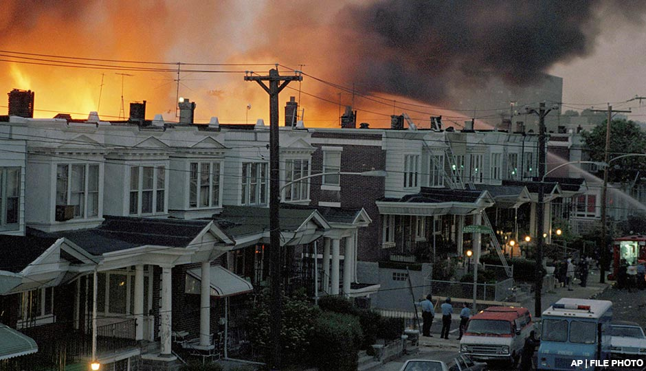 In this May 1985 photo, scores of row houses burn in a fire in the west Philadelphia neighborhood. Police dropped a bomb on the militant group MOVE's home on May 13, 1985 in an attempt to arrest members, leading to the burning of scores of homes in the neighborhood.