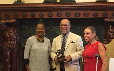 Kelly Lee, Jerry Pinkney, and Sheila Hess pose with the award that was presented to Pinkney this afternoon.
