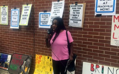 Ramona Africa standing in front of posters supporting Mumia Abu-Jamal
