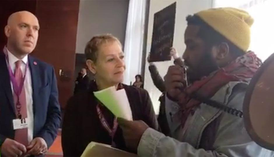 Screenshot of Abdul-Aliy Mohammad reading a list of demands to Nurit Shein and Michael Weiss.