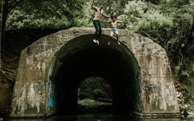 couple jumping off a bridge