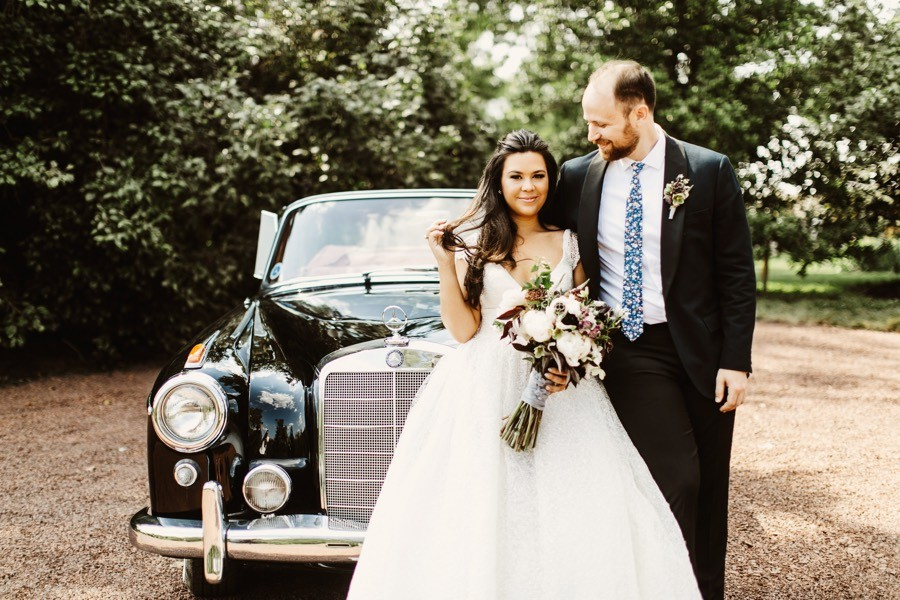 bride and groom with vintage getaway car