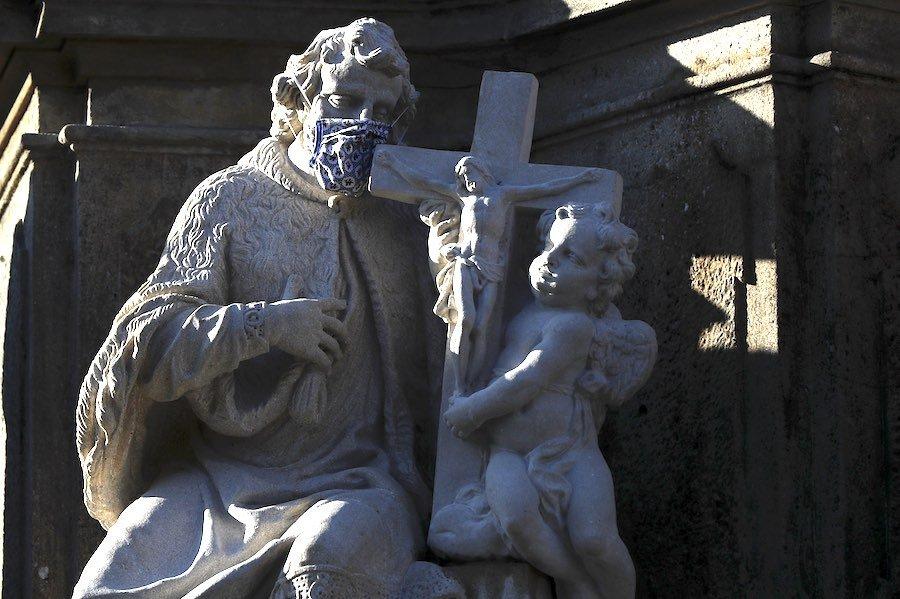 a czech statue wearing a face mask during the coronavirus crisis
