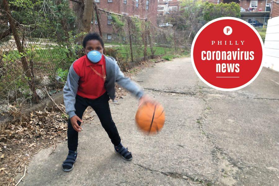 A young masked boy plays basketball during the Philadelphia coronavirus crisis