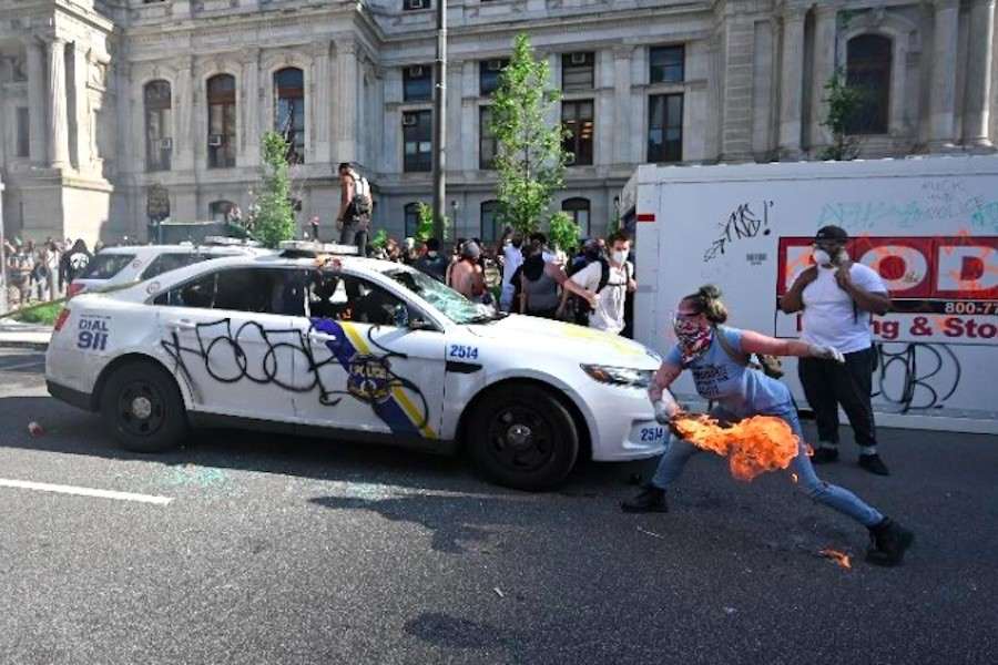 the FBI says this photo shows Lore Blumenthal lighting a Philadelphia police car on fire during a George Floyd protest