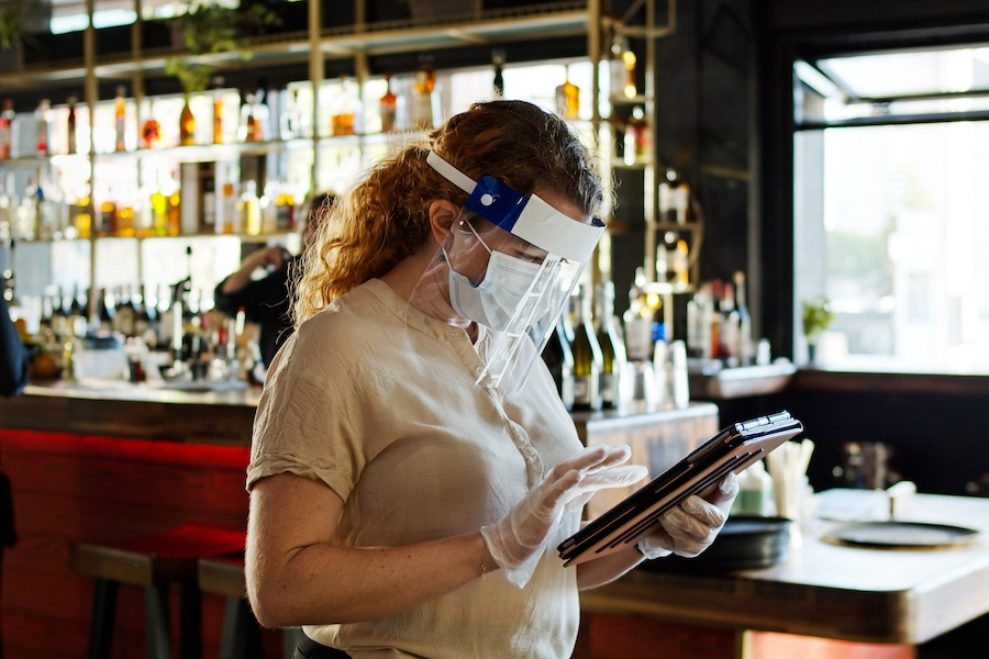 a server wearing a mask and face shield, as all servers are required to do when indoor dining returns to Philadelphia restaurants