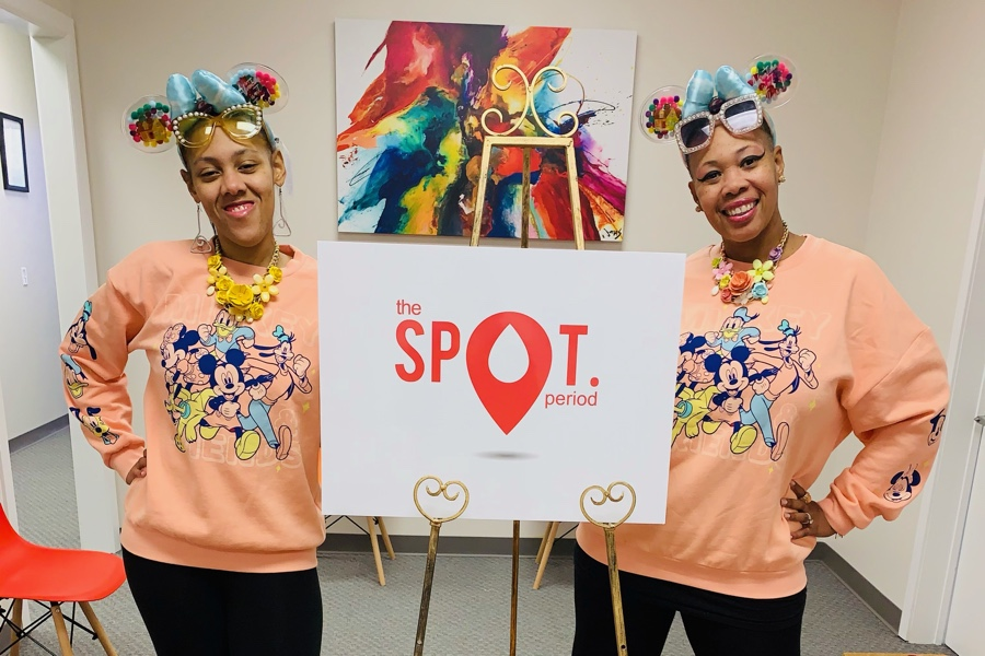 Lynette and Nya in front of a sign that says The SPOT Period