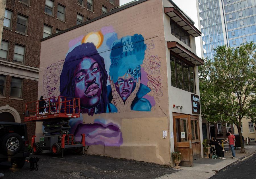 ash ryan working on the lil nas x mural in philadelphia