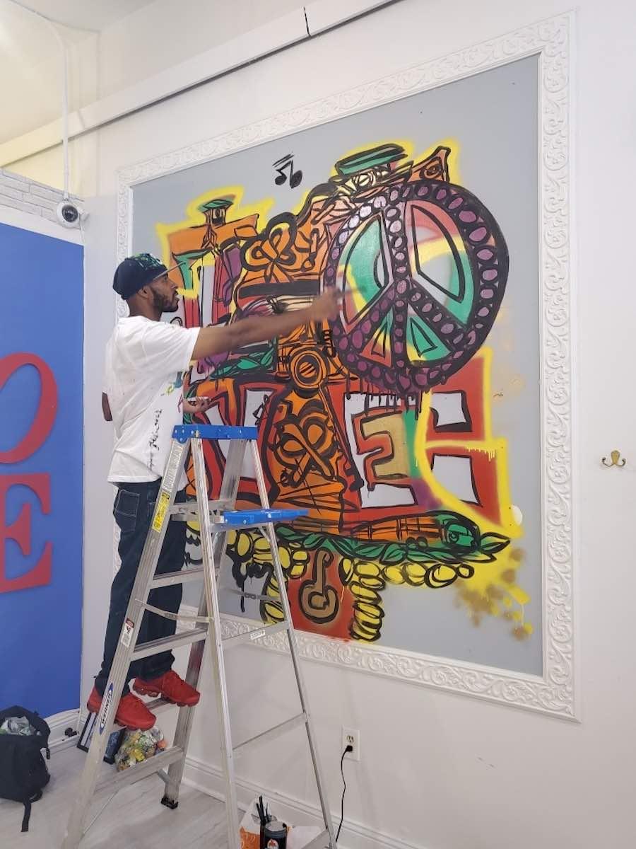 philadelphia street artist jalapeno miles working on a mural inside InstaPhilly