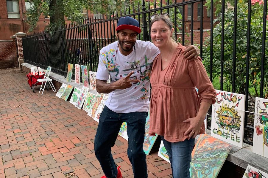 philadelphia street artist jalapeno miles with a woman who tracked him down after he left a painting in the lobby of her building