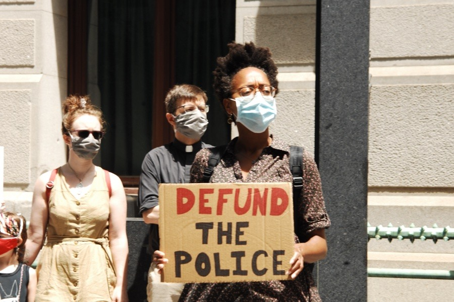 """a protester holds a sign that says """"Defund the Police"""""""